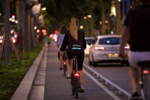 women riding a bike wearing Active Lights for electric vehicle safety clothing and garments.